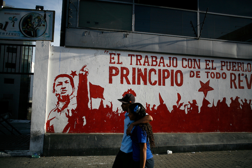 A couple walks past a mural showing President Hugo Chavez in downtown Caracas.