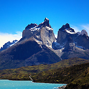 A road winds along the shore of Lago Pehoe in Torres del Paine, Chile as Los Cuernos (The Horns) stand in the background.