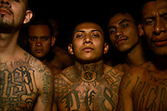 Members of the Mara 18 gang incarcerated in Izalco men's prison in El Salvador pose for a portrait inside their overcrowded cell.