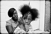 A woman braids the hair of a young girl sucking her thumb, Rockaway Beach, Queens, NY.