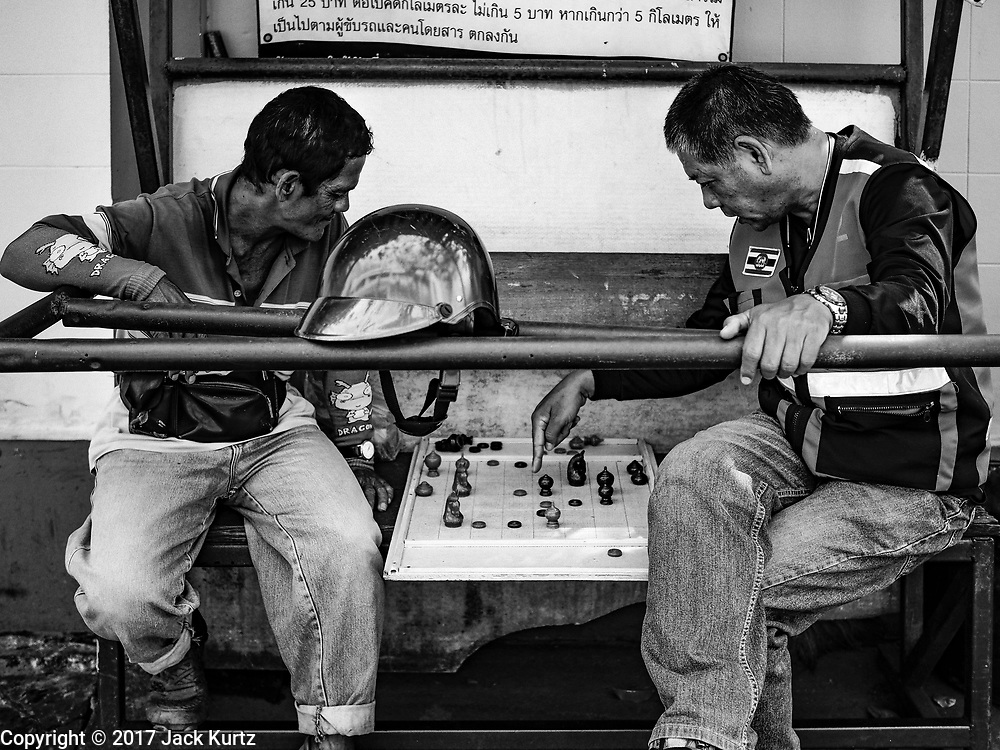 """04 ARIL 2017 - BANGKOK, THAILAND: Motorcycle taxi drivers (called """"motosai"""" locally) play chess while they wait for fares in the Thonburi section of Bangkok.       PHOTO BY JACK KURTZ"""