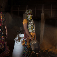 Women work long and hard days in a corn mill in the docks of Chittagong in Bangladesh. They wear a cover to mask the dust that is all around them