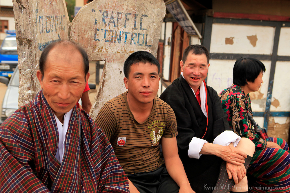 Asia, Bhutan, Wangdue. Three men sitting on corner in Wangdu Phodrang.
