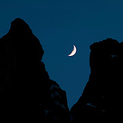 The Early Winters Spires, located in Washington's North Cascades, frame a crescent moon. The spires, the tallest of which is more than 7,800 feet, are located at Washington Pass, about 30 miles west of Winthrop.