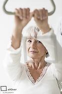 Seniorin haelt sich am Haltegriff eines Krankenbettes (model-released)