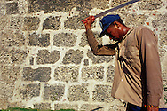 Un hombre trabajando bajo el sol, junto a la muralla con un machete en la mano. Por su uniforme, está encargado de mantener limpia la región cercana a la muralla. Cartagena de Indias, 2001 (Ramón Lepage / Orinoquiaphoto)     The fortified wall of Cartagena is in excellent condition and stretches more-or-less unbroken round a good portion of the Old Town. It is a pleasure for locals well as visitors to walk and observe the colonial architecture and excellent view of the Caribbean ocean..