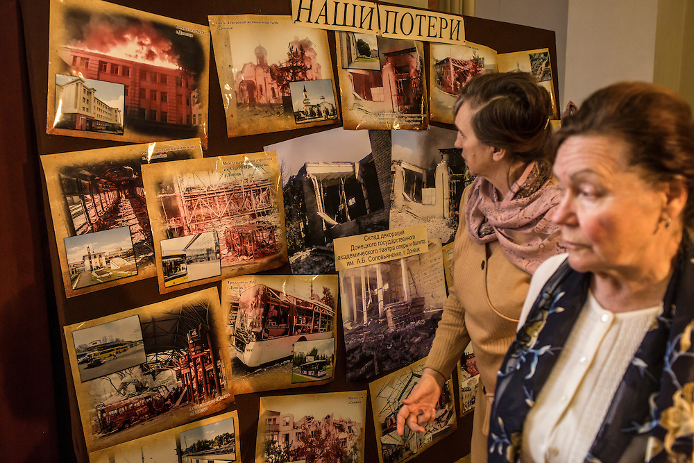 Women view a display of war damage in the lobby of the Donbass Opera on Saturday, March 26, 2016 in Donetsk, Ukraine.
