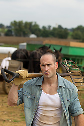 man on a working farm with a pitch fork over his shoulder