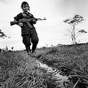 Marie Sol a female FARC recruit armed with a Kalashnikov assault weapon on patrol near her camp in Caqueta.<br />