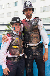 """London, August 24th 2014. Police officers maintain their good humour despite being covered in paint as thousands of Londoners of all races and cultures attend Notting Hill Carnival's """"Family friendly"""" day ahead of the main carnival on August Bank Holiday Monday."""