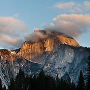 The granite monolith of Half Dome (8836 feet or 2693 meters elevation) is a famous symbol of Yosemite National Park, Sierra Nevada, California, USA. The peak rises 4737 ft (1444 m) above the valley floor. Designated a World Heritage Site by UNESCO in 1984, Yosemite is internationally recognized for its spectacular granite cliffs, waterfalls, clear streams, Giant Sequoia groves, and biological diversity. 100 million years ago, the Sierra Nevada crystallized into granite from magma 5 miles underground. The range started uplifting 4 million years ago, and glaciers eroded the landscape seen today in Yosemite. Panorama stitched from 3 overlapping photos.