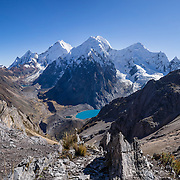 "Cordillera Huayhuash panorama from San Antonio Pass (5000 meters or 16,4000 feet) includes left to right: pyramidal Yerupaja Grande (6635 m or 21,770 ft, highest peak in the Amazon basin); Nevado Serapo with Siula Grande (6344 m or 20,800 ft) rising behind; and Nevado Carnicero (5960 m). Below is turquoise lake Juraucocha at 4343 m. Day 6 of 9 days trekking around the Cordillera Huayhuash in the Andes Mountains, Peru, South America. Siula Grande was the subject of the gripping 2003 British docudrama ""Touching the Void."" In 1985, climbers Joe Simpson and Simon Yates scaled the treacherous Siula Grande, but after Joe broke his leg, their descent became one of the most amazing survival stories in mountaineering history. The 2003 movie is based upon Joe Simpson's harrowing book, ""Touching the Void: The True Story of One Man's Miraculous Survival."" This panorama was stitched from 9 overlapping photos."