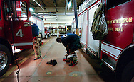 Newburgh firefighters Chris Odell (left) and Jason Blackwell (right) remove their turnout coats in the firehouse after firefighters responded to an automatic alarm at Mount Saint Mary College at 3:30AM in Newburgh, NY on Tuesday, June 28, 2011. The Newburgh Fire Department responds to nearly 3,000 calls a year.