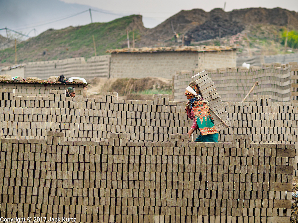 03 MARCH 2017 - BAGMATI, NEPAL:  Workers carry unbaked bricks from the fields where they're molded to a kiln for drying at a brick factory in Bagmati, near Bhaktapur. There are almost 50 brick factories in the valley near Bagmati. The brick makers are very busy making bricks for the reconstruction of Kathmandu, Bhaktapur and other cities in the Kathmandu valley that were badly damaged by the 2015 Nepal Earthquake. The brick factories have been in the Bagmati area for centuries because the local clay is a popular raw material for the bricks. Most of the workers in the brick factories are migrant workers from southern Nepal.      PHOTO BY JACK KURTZ