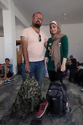 Tarik Aljadoue (34) and his wife Samar Jamal (27) at the space that NGO Aggalia has organised as a temporary stop for refugees in Kaloni village, as they are on their way to Mytilene city. A local person drove them there the night before. The couple is from Alepo in Syria where Tarik was working as an IT engineer for a French owned oil company until they closed down their business there in 2011. Since 2011 he moved to Kafarhamra north of Alepo, as his house in Alepo was in a dangerous area. He got married to Samar one year ago and they were waiting to see what will happen to their country. 6 months ago internet was cut so it was difficult to learn any news of what was really happening. Local TV was only broadcasting propaganda from different armies. On Friday one week ago, they decided to find a safe country to have their children and leave Syria where they saw no work and no future as they could not see the end of this war. They want to try to reach Germany or any other European country where they can find work. <br /> Their trip started from Alepo to Tartus by bus, then on an other bus to a port from where they boarded a ship for one and a half day to Toshojo port (Tasucu port?) in Turkey near Mersin. From there they took a bus for 13 hours to Izmir but before they arrive they heard that there were police checks in Izmir and as soon as they arrived, they boarded an other bus for 9 hour to Istanbul. There they stayed for two days until the smugglers told them that they could start their trip to Greece. They payed 1250 USD each and after two days, at 8 am, they met the smugglers at a metro station, they boarded a bus with 60 people and no AC and they traveled to a location near Izmir. The trip lasted for 7 hours and it was unbearably hot. When they got off the bus somewhere near the sea, they were told to switch off their mobile phones and walk for one hour until they reached the sea. There there were three dinghy boats with engines and 33 to 40 people would board o