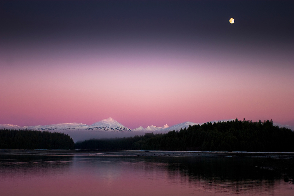 A full moon rises over a purple and pink sunset near the headquarters of Glacier Bay National Park.