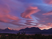 """The last rays of sunset brighten lenticular clouds with pink and magenta color over Aoraki / Mount Cook, (3755 meters or 12,349 feet) in Aoraki / Mount Cook National Park, South Island, New Zealand. In 1990, UNESCO honored Te Wahipounamu - South West New Zealand as a World Heritage Area. Published in """"Light Travel: Photography on the Go"""" by Tom Dempsey 2009, 2010."""