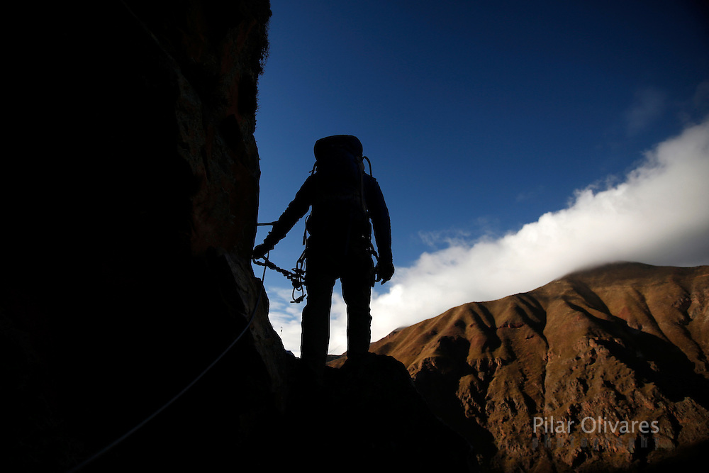 Ario Ferri, creator of the Skylodge Adventure Suites, climb to reach the three cabines hotel in the Sacred Valley in Cuzco, Peru, August 14, 2015. The Skylodge is composed by three capsule suites hanging at the top of the 1300 feet mountain with a 300 degree view of the Valley. To sleep at Skylodge, people must climb 400 meters of Via Ferrata path and to leave the hotel people go down  a trail through ziplines. REUTERS/Pilar Olivares