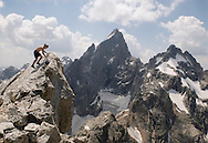 "Sam Coffin gingerly tags the 12.325-foot summit of Teewinot Mountain in Grand Teton National Park. The mountain, the northern-most spire of peaks known as the Cathedral Group, is named with the Shoshone Indian word meaning ""many pinnacles."" The Teton Glacier is visible below the Grand's North Face."