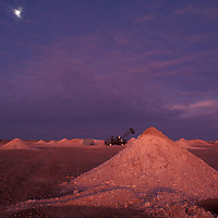 Australia, South Territory, Evening twilight lights opal mine tailings piles in the Outback mining town of Coober Pedy