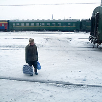 A passenger carries his baggage through the RR yard.