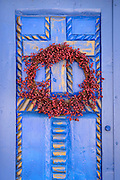 Blue door and red wreath at La Casita de Kaleidoscopes in Old Town Albuquerque, New Mexico.
