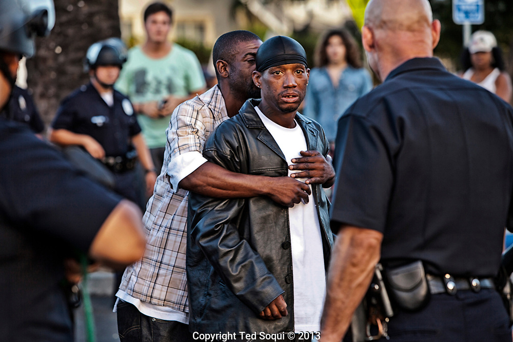 A protester angry at police is restrained by his friend.<br /> Protesters march through out South Los Angeles in response to the not guilty verdicts in the Trayvon Martin verdict in Florida.