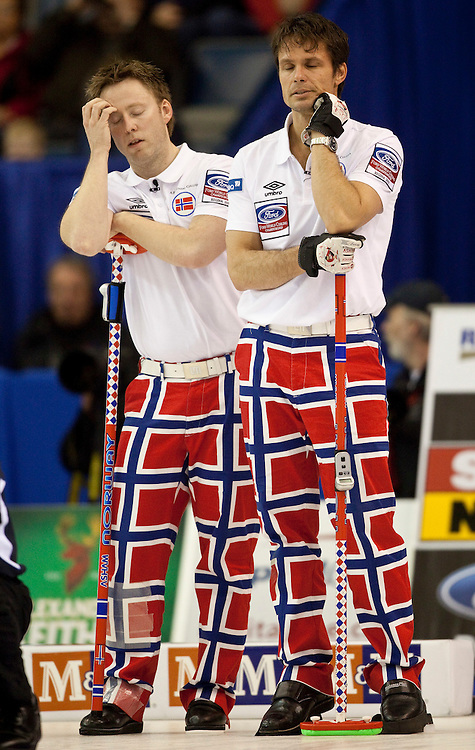 Norwegian skip Thomas Ulsrud, right and third Torger Nergaard react as Scotland makes a shot during their 7-6 loss in the semi-final at the Ford World Men's Curling Championships in Regina, Saskatchewan, April 9, 2011. The Scottish team will face Canada in the final Sunday.<br /> AFP PHOTO/Geoff Robins