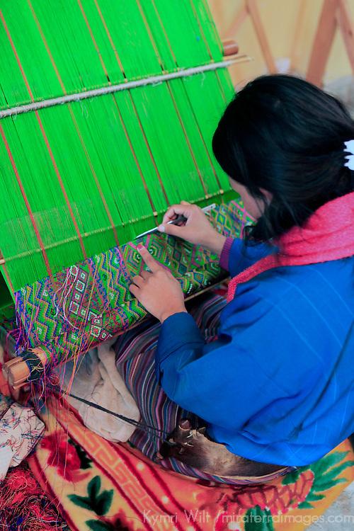Asia, Bhutan, Paro. Bhutanese woman weaves traditional kira.