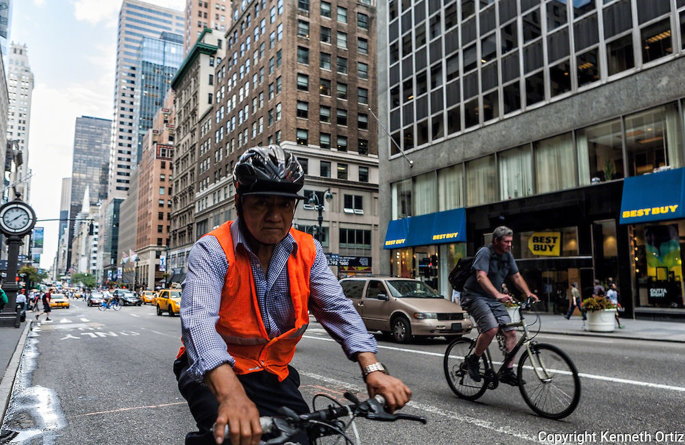 Two bicyclists riding down 5th Avenue in New York City.