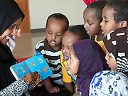 Seattle, Washington: May 15, 2012.  Group of Somali preschoolers attentively listen and repeat numbers which a teacher points out in a book. Words in the book are both in English and their native African language.