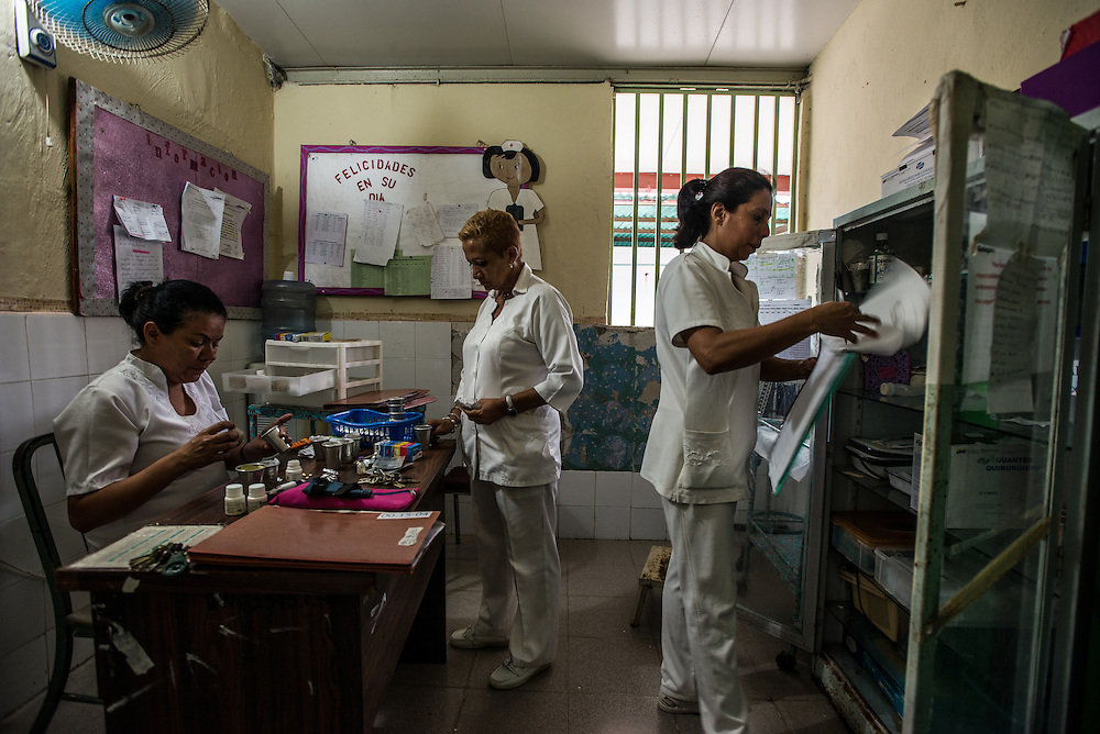 BARQUISIMETO, VENEZUELA - AUGUST 24, 2016: Head nurse, Évila García, (center) debates with other nurses about which patients are the most unstable, to decide which patients will receive the limited number of pills on hand, and which will go without. The hospital has not employed a psychiatrist in over two years, so even though they are not doctors, the nursing staff find themselves responsible for doing a psychiatrist's work - they make decisions about how to medicate patients - modifying doses and swapping one patient's pills to give to another, who might be more unstable and need them more. They reference medical files from two years ago when a licensed psychiatrist was on staff - all written by hand and kept in paper folders. They use a mix of the old treatment plans from two years ago, plus their own observations of the patient, and modify treatments and care based on years of learning from trial and error.   The economic crisis that has left Venezuela with little hard currency has also severely affected its public health system, crippling hospitals like El Pampero Psychiatric Hospital by leaving it without the resources it needs to take care of patients living there. Drugs used to combat bipolar disorder, epilepsy, schizoaffective disorder and chronic anxiety are now in short supply, as are numerous sedatives and tranquilizers needed to care for patients. When a patient loses control, often the only thing they can do is lock them in an isolation cell to prevent them from hurting themselves, other patients and members of the staff.  PHOTO: Meridith Kohut