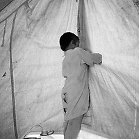 Mohammad Rafique closes the tent while the midwife examen's his mother and checks the growth and position of the baby. Karachi, Pakistan, 2010