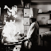 A chef working with a flaming pan in the kitchen of an Indian restaurant.