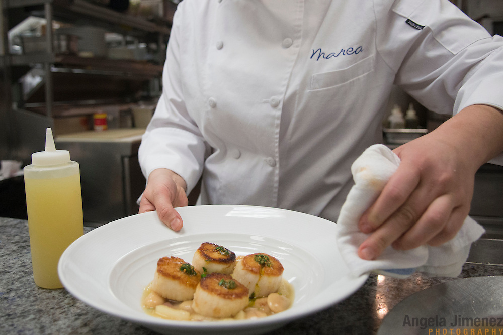 20330319AJ  <br /> <br /> Lauren DeSteno, originally from New Jersey, a sous chef at Marea in New York City, is photographed in the dining room of the restaurant on March 19, 2013. <br /> <br /> She was plating an original dish of hers, scallops with saut&eacute;ed turnip greens, corona beans, speck and preserved lemon. <br /> <br /> <br /> photo by Angela Jimenez/ for The Star-Ledger