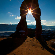 The late afternoon sun shines through Delicate Arch, a freestanding natural arch in Arches National Park, Utah. The arch, approximately 65 feet (20 meters) tall, was carved by the wind from an Entrada sandstone fin.