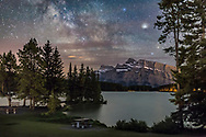 The Milky Way in Sagittarius and Scorpius, low in the south, over Mt. Rundle in Banff, Alberta, from the shore of Two Jack Lake, June 3, 2016. Saturn is the bright object at upper right, then in Ophiuchus just above Scorpius. Some thin cloud fuzzed the images of Saturn and stars. The foreground is partly illuminated by car headlights, to light up the green landscape. Wind made the water rough and unreflective.<br /> <br /> This is a stack of 4 x 25 second exposures (mean combined to smooth noise) for the ground and a single 25-second exposure for the sky, untracked but with just slight trailing. All at f/2.2 with the 35mm lens and Canon 6D at ISO 3200. Shot as part of a 280-frame time-lapse and star trail sequence, though that was partly ruined by the car headlights. Here they help somewhat.