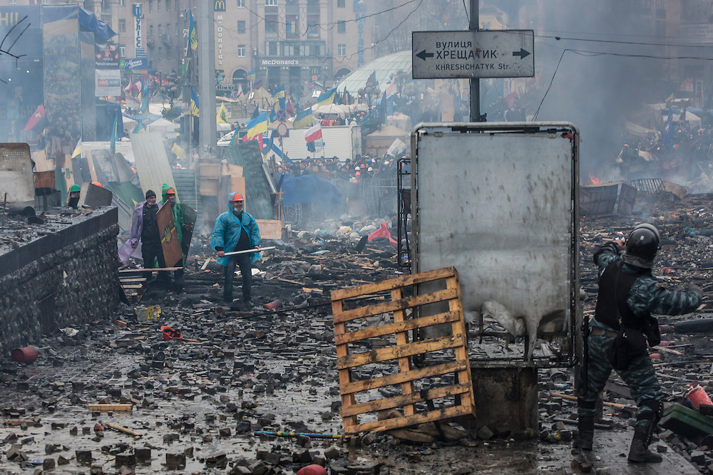 KIEV, UKRAINE - FEBRUARY 19: A Berkut riot police officer throws a stone at anti-government protesters, who were throwing rocks in return, on Independence Square on February 19, 2014 in Kiev, Ukraine. After several weeks of calm, violence has again flared between anti-government protesters and police as the Ukrainian parliament is meant to take up the question of whether to revert to the country's 2004 constitution. (Photo by Brendan Hoffman/Getty Images) *** Local Caption ***
