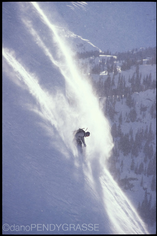 A snowboarder slashes a steep powdery face in the Coast Mountains of British Columbia.