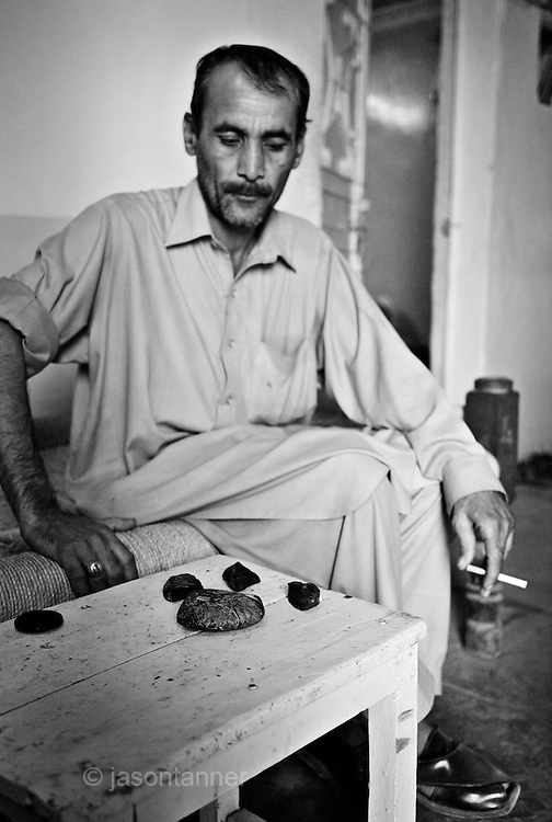 A dealer shows of raw opium for sale at his his in Peshawar..Record opium crops in neighbouring Afghanistan have resulted in a cheap, affordable and plentiful supply of heroin and opium in Pakistan...In the frontier town of Peshawar, a gram of heroin sells for 100 rupees, little more than a dollar. Most addicts smoke or ?chase the dragon?, some inject but the inaccessibility of syringes dictate most addicts smoke the drug...Opium can be found in its pure form, fresh from record harvests in Afghanistan. Most is processed into heroin in the many factories along the Afghan / Pakistan borer, but some is retained, especially in the tribal province, for ?traditional medicinal? purposes such as bile din tea for curing arthritis and flu symptoms...Along the Peshawar ? Islamabad road addicts prepare heroin for smoking and injecting in full view of passers by on one of the countries busiest roads..