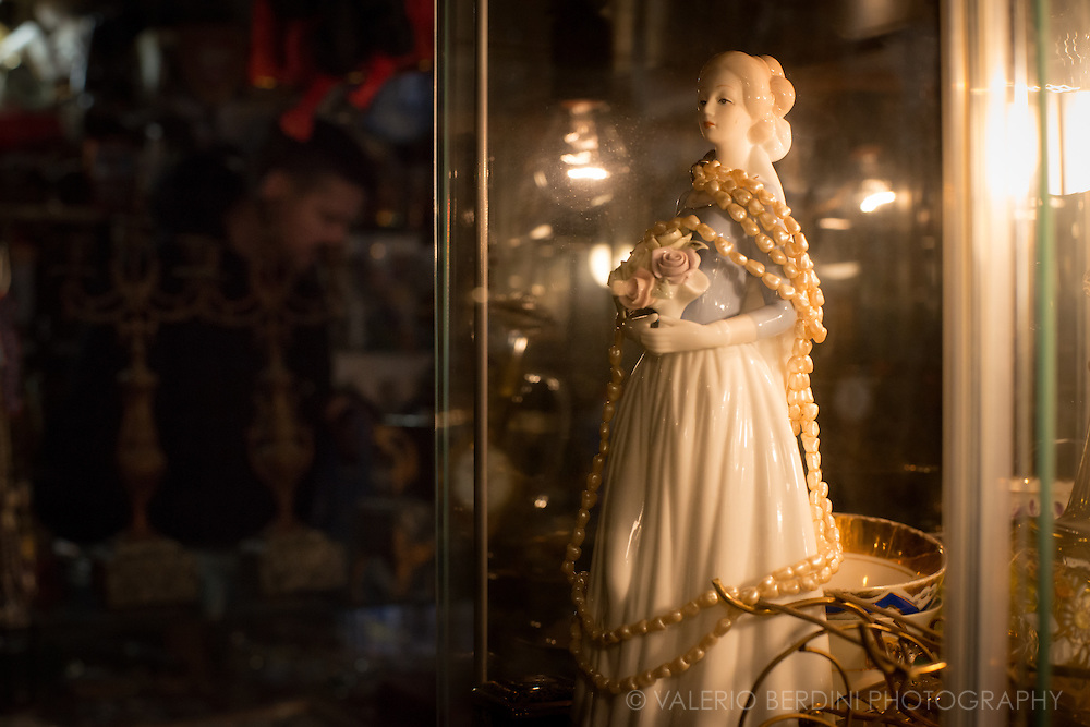 A porcelain statue waiting in a window o be sold in an antiques shop in Prague
