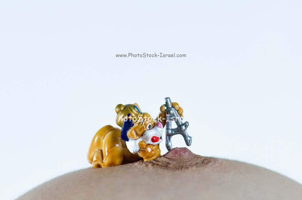 miniature toy measuring woman's nipple