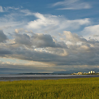 Perched at the edge of the Alaskan wilderness, the Anchorage skyline glistenes in the early light as viewed from the Tony Knowles Coastal trail near Pt. Woronzof.