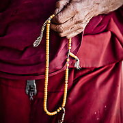 An old Buddhist monk counts prayer beads.