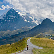 """From Männlichen Gipfel, a wide vista sweeps from left to right: Grindelwald Valley, Wetterhorn, Eiger (middle pyramid, the Ogre 13,026 feet elevation), and Lauterbrunnen Valley in the Berner Oberland, Switzerland, the Alps, Europe. A gondola (gondelbahn) connects Grindelwald with Männlichen, where a cable car goes down to Wengen (Luftseilbahn Wengen-Mannlichen). From Mannlichen station, walk uphill 15 minutes for a stunning view. The world's longest continuous rack and pinion railway (Wengernalpbahn) goes from Grindelwald up to Kleine Scheidegg and down to Wengen and Lauterbrunnen. From Kleine Scheidegg, another cog train (Jungfraubahn) ascends steeply inside the Eiger to Jungfraujoch, the highest railway station in Europe. Two vertical miles (3000 meters) of mountain rise from valley bottom to Eiger top. UNESCO lists """"Swiss Alps Jungfrau-Aletsch"""" as a World Heritage Area (2001, 2007). Panorama stitched from 7 images. Published 2.4 meters wide on a private kitchen backsplash in Switzerland 2009. Published in """"Light Travel: Photography on the Go"""" book by Tom Dempsey 2009, 2010."""