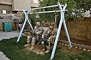 U.S. Army Spec. Matthew Andrews and Spec. Mike Lyall with the 3rd Stryker Brigade Combat Team, take a break in the courtyard of an Iraqi's house during a cordon and search for weapons caches and anti-Iraqi forces in Old Baqubah, Iraq, on April 4, 2007.