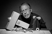 Portrait of wood artist Doug Lamont at his drafting table with tools, prototypes, and drawing.