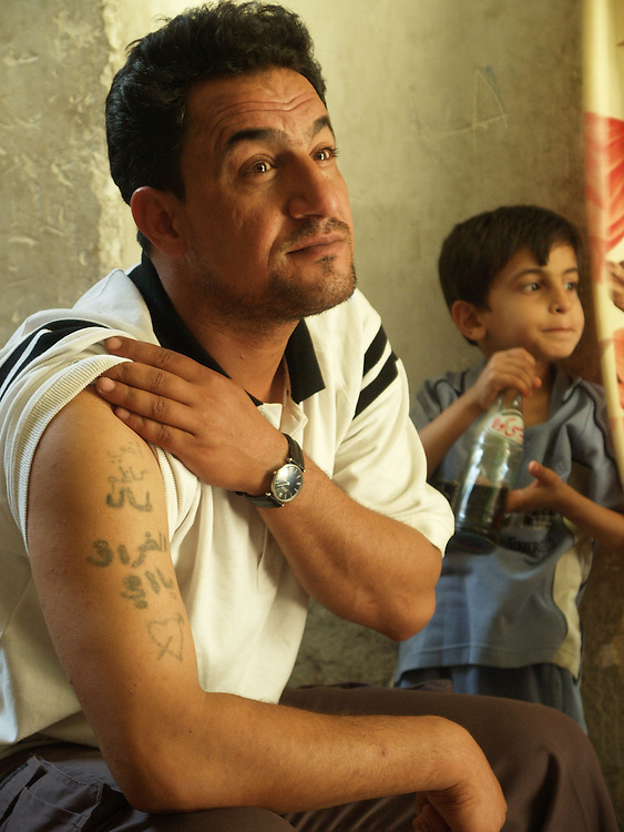 6 April 2004..Baghdad, Iraq...Victim of abuse in Abu Ghraib...Hashim Mohsin Lazim aged 34 in his home in Sadr city with his 7 year old son Mohamed...Hashim was arrested by US forces last year and spent a period of time in the now notorious Abu Ghraib prison complex...He claims he is one of the prisoners who appears in the photos currently making news around the world...He relates accounts of abuse at the hands of US forces based in the complex. This abuse includes being photographed naked in the presence of female US soldiers....His distinctive tatoos would be visable in the pictures he claims if they were sufficiently enlarged and enhanced.