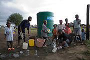Adults and Children in the suburb of Budiriro outside of Harare queue to collect clean water in containers brought to collection points where water bowsers have been supplied by NGO's such as UNICEF. ..