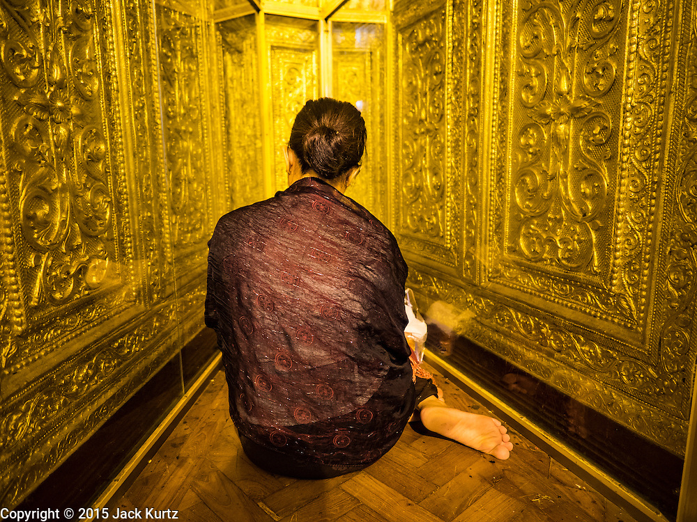 28 OCTOBER 2015 - YANGON, MYANMAR: A woman prays in a niche in Botataung Pagoda during observances of Thadingyut in Yangon. Botataung Pagoda was first built by the Mon, a Burmese ethnic minority, around the same time as was Shwedagon Pagoda, over 2500 years ago. The Thadingyut Festival, the Lighting Festival of Myanmar, is held on the full moon day of the Burmese Lunar month of Thadingyut. As a custom, it is held at the end of the Buddhist lent (Vassa). The Thadingyut festival is the celebration to welcome the Buddha's descent from heaven.     PHOTO BY JACK KURTZ